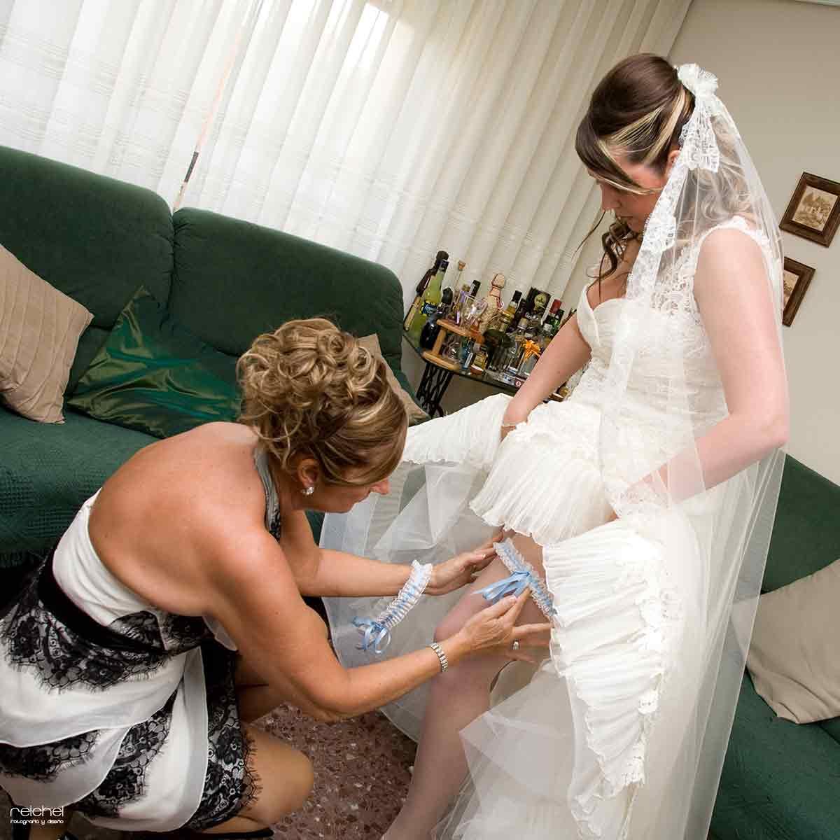 madre de la novia poniendo la liga a su hija